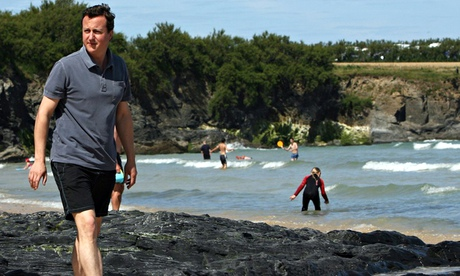 David Cameron in shorts and a polo shirt on the beach in Cornwall