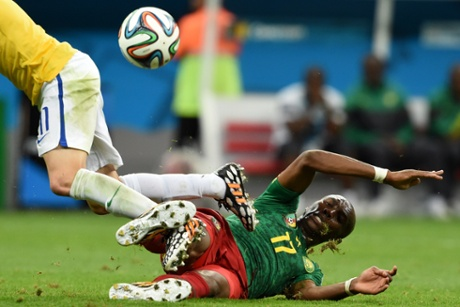 Brazil's midfielder Oscar is tackled by Mbia.