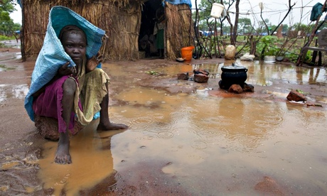 A Sudanese refugee sits outside her hut on a rainy afternoon at the Yida refugee camp