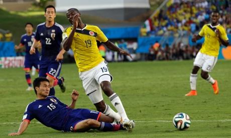 Japan's Yasuyuki Konno fouls Colombia's Adrian Ramos to give away a penalty.