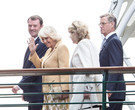 HRH The Duchess of Cornwall waves as she walks across a bridge that connects the Players Lawn to Centre Court.
