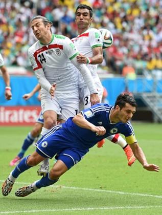 Emir Spahic of Bosnia and Herzegovina falls as Andranik Teymourian and Mehrdad Pooladi of Iran go up for a header.