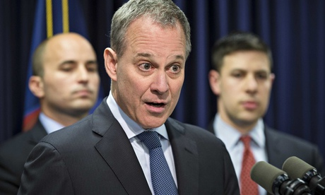 Eric Schneiderman in suit and tie speaks into a microphone at a press conference