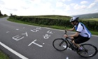 A cyclist approaches a slogan written in Yorkshire slang.