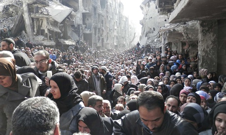 Residents wait to receive UN food aid at the al-Yarmouk camp