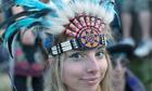 Glastonbury reveller in headdress at the Stone Circle