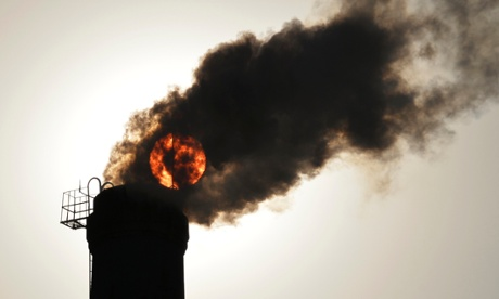 The sun is seen behind smoke billowing from a chimney of a heating plant in Taiyuan, Shanxi province