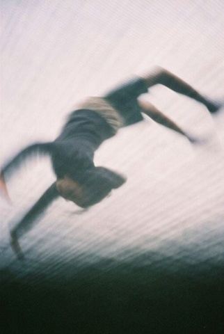 a girl mid back flip whilst on a trampoline