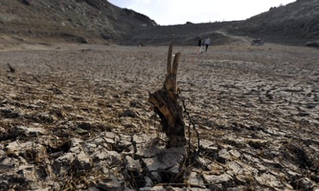 Yemenis walk through a drought-affected dam on the outskirts of Sana'a, Yemen.  Sana a city is running out of water and many relief agencies feel that it could become the first capital city in the world to run out of a viable water supply.