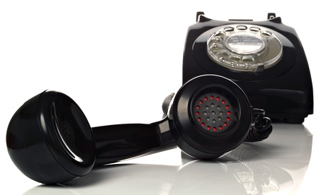 A retro black phone with the handset off the hook