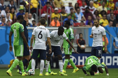 Referee Mark W Geiger shows the yellow card to France's midfielder Blaise Matuidi after a bad challenge on Ogenyi Onazi.