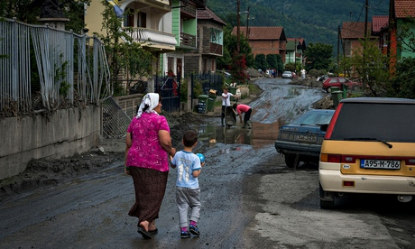 A woman leads a child wearing a football shirt bearing Edin Džeko's name through a flood-hit settlem