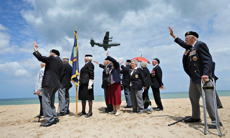 D-day veterans on Sword Beach as a military aircraft flys past