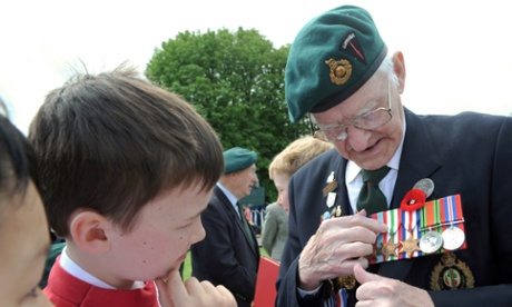 Veteran Frederick Wyatt, 92, from the 48th Royal Commando Dragoon Guard, explains the meaning of his decorations to a choir boy of the St John's College Choir of Cambridge, in Bayeux.