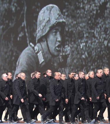 Performers take part in a stage show in front of archive footage during the international ceremony at Sword Beach.
