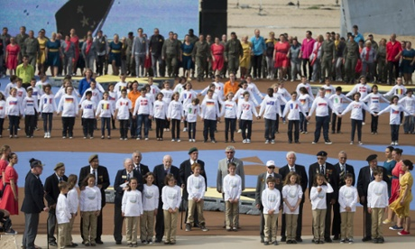Veterans stand to attention flanked by children during an international D-day commemoration ceremony on the beach of Ouistreham.