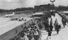 A crowd of people watching the arrival of the Queen at the official opening of Gatwick Airport, 9 June 1958