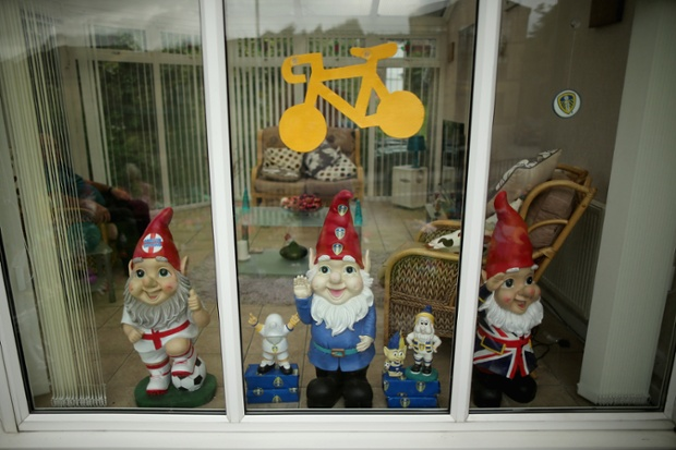 Giant gnomes and a yellow bike decorate the window of a house in Haworth