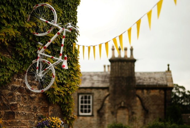 A bicycle decorated with polka dots hangs from the wall of a pub on the route of the Tour de France in Addingham