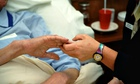 A hospice worker holds a patient's hand