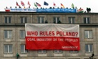 Greenpeace activists with international flags and banners stand on the roof of the Ministry of Economy in Warsaw, Poland