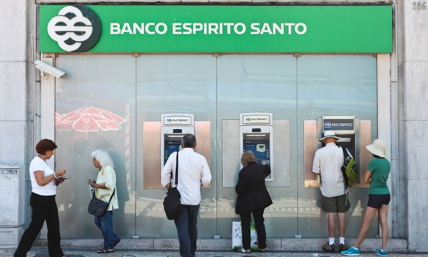 People withdraw money from ATM machines in a Banco Espirito Santo (BES) branch in Lisbon, Portugal, 10 July 2014.