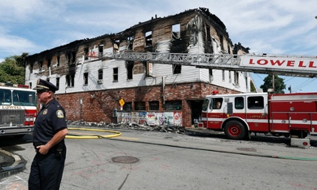 A policeman secures the scene of a burned three-story apartment and business building in Lowell.