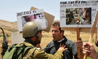 A Palestinian protester argues with an Israeli army soldier