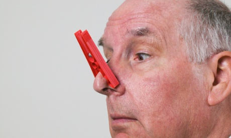 Senior man looking down at plastic clothes peg on nose, close-up bad smell