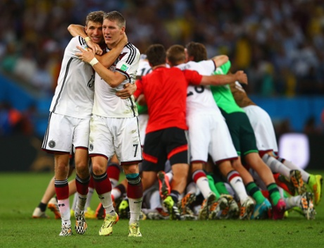 Thomas Muller, left, and Bastian Schweinsteiger have a celebratory hug as their team-mates form a  celebratory huddle behind.