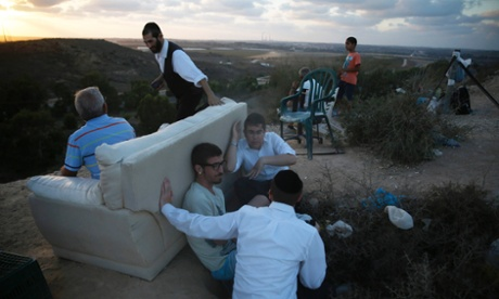 Israelis gather to look at the Gaza Strip from a hilltop near the southern town of Sderot.