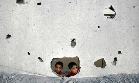 Palestinian children look through the ruin of Gaza prison building destroyed by Israel attacks.