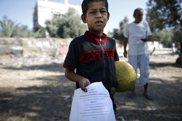 A Palestinian boy shows a flyer dropped over Gaza City by the Israeli army urging residents to evacuate their homes.