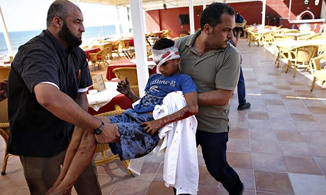 Palestinian al-Deira hotel employees carry a wounded boy - gaza port shelling