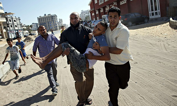 Employees of Gaza City's al-Deira hotel carry a wounded boy following a strike - gaza port shelling