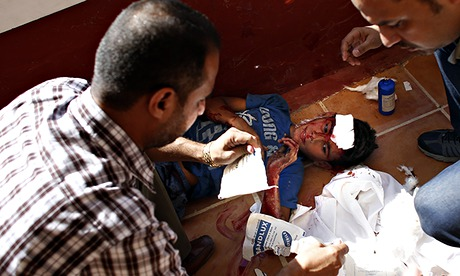 Employees of Gaza City's al-Deira hotel take care of a wounded boy -  gaza port shelling