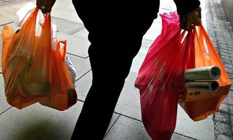 A woman carries her shopping in plastic bags