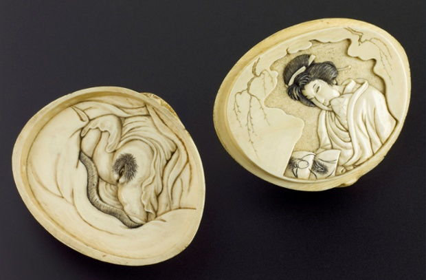 Oriental ivory shell, divides into two halves, on one half is  a female genitalia, on the other is a carving of a female looking at an erotic picture.