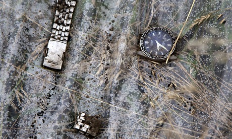 A broken watch lies on a plastic cover at the site of the Malaysia Airlines crash