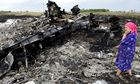 A resident surveys the wreckage at the Flight MH17 crash site in Ukraine.