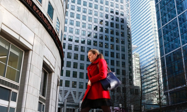A worker walks past the Reuters office in the Canary Wharf business district in London February 26, 2014.