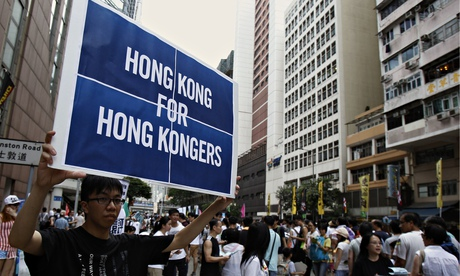 A protester carries a placard during a mass protest demanding universal suffrage in Hong Kong