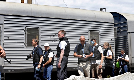 OSCE inspectors, part of the monitoring mission to Ukraine, document bodybags from MH17 in a refrigerated wagon at Torez train station, near the crash site, on Sunday. Photograph: Robert Ghement/EPA