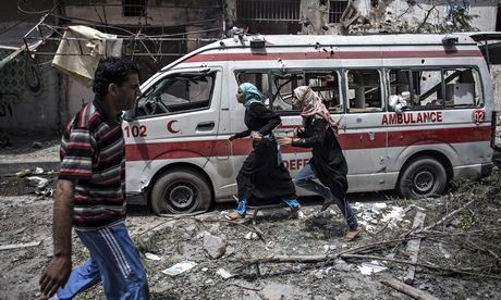 Two Palestinian girls run past a damaged ambulance in Gaza