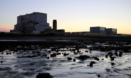 The sun sets behind EDF's Hinkley Point B (left), and Hinkley Point A (right) nuclear power stations beside the Bristol Channel