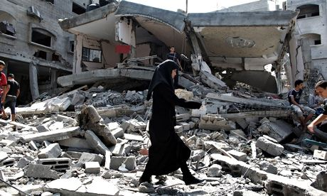 A woman walks on debris in Gaza