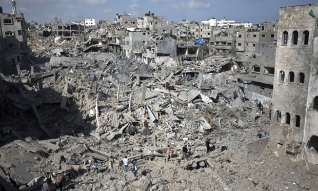 Palestinians walk across the rubble of destroyed buildings and homes in the Shejaiya residential district of Gaza City.