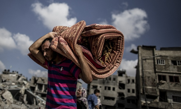 A Palestinian man walks with a mattress rolled on his back while leaving the northern district of Beit Hanoun in the Gaza Strip.