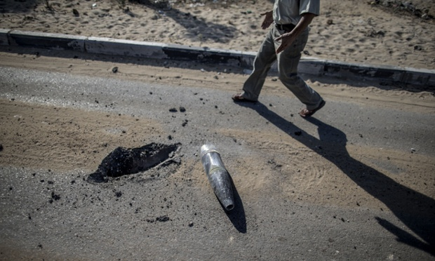 A Palestinian man walks past a unexploded tank shell while walking back towards the northern district of Beit Hanun in the Gaza Strip.