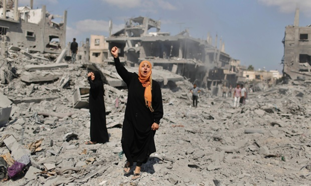 A Palestinian woman chants slogans in support of Palestinian fighters as she stands next to her destroyed house in Beit Hanoun town.